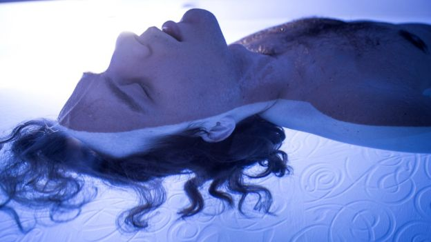 Close up photo of man floating in float tank